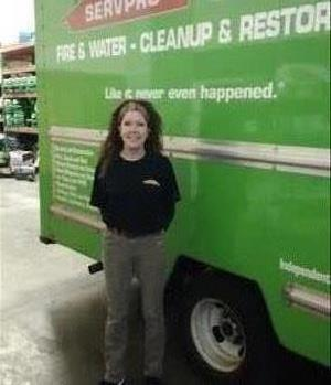 Female employee standing next to a green SERVPRO vehicle