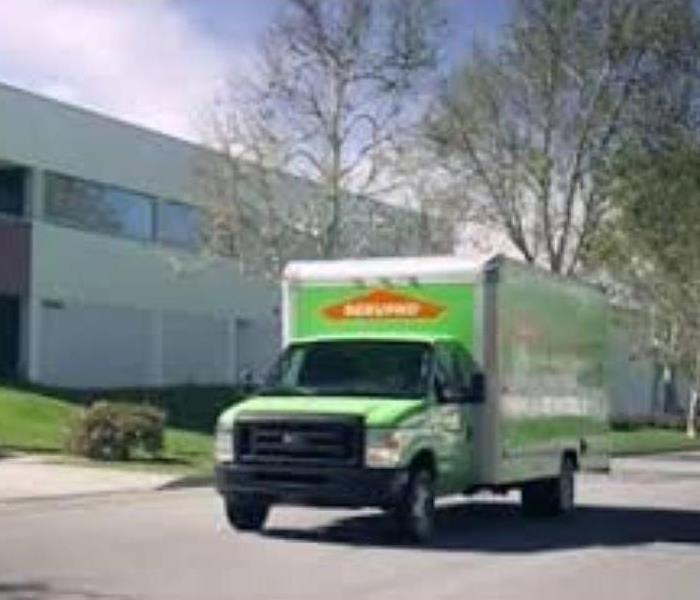 Green SERVPRO truck in front of commercial building